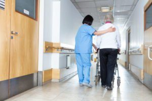 nursing home nurse assisting resident with walker