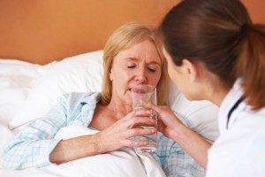 nurse giving nursing home resident water