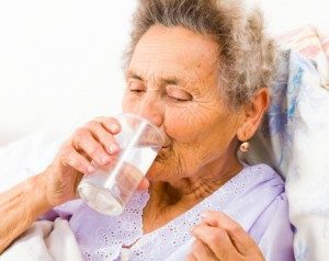 nursing home patient taking medication with water