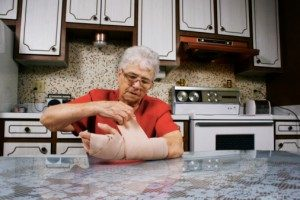 person wrapping a wound at home