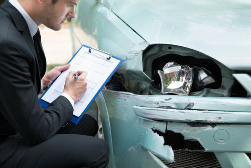 insurance adjuster taking notes at car accident