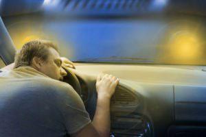 man who has fallen asleep at steering wheel
