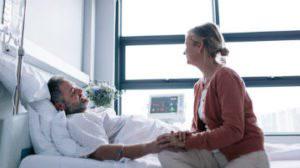 Injured man in hospital bed talking to nurse about seeking punitive damages