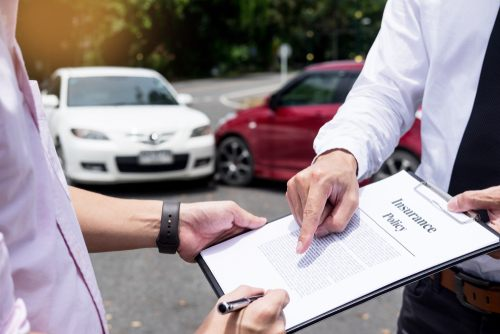 man signing insurance claim form held by insurance adjuster